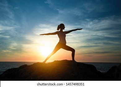 Yoga woman meditating in Assane the Warrior position. Silhouette on the sea coast during a beautiful sunset.