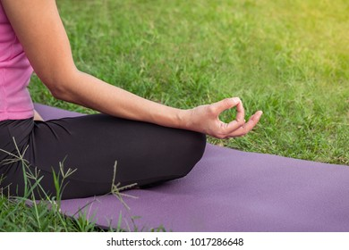 Yoga woman meditating in lotus posture at the park
