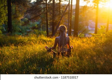 Yoga woman meditating on picturesque glade in a green forest.