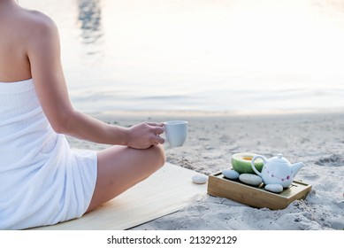 Yoga woman meditating at serene beach sunset