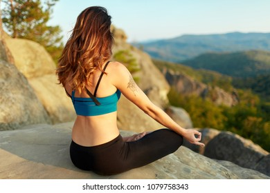 Yoga woman, meditation. Rearview shot of a fit and toned sportswoman meditation in the mountains practicing yoga outdoors concentrating breathing asana yoga fitness toning body beauty health vitality