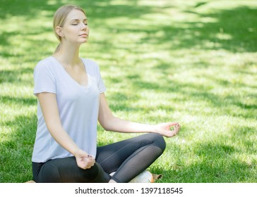 yoga woman on green grass.girl sitting in meditation in the Park in summer