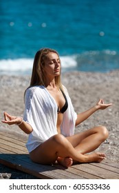 Yoga woman on sand beach - Young slim body woman at tropical beach vacation. Meditating girl enjoy summer vacation alone on beach in yoga pose. Fitness model in zen pose outdoors at summer shore.