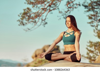 Yoga woman. Yoga poses. Portrait of a beautiful young woman meditation in peace of nature sitting on top of a rock in the mountains beauty lifestyle sensuality femininity relaxation