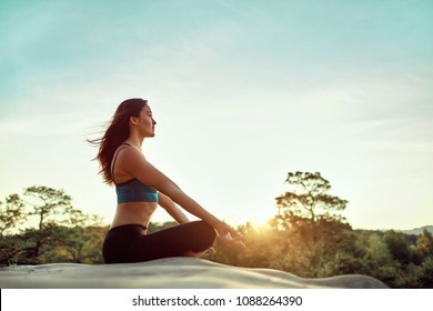 Yoga woman. Yoga poses. Silhouette of an athletic sportswoman sitting in lotus position meditating during sunset. Happy and healthy woman practiving yoga on sunset outdoors,  meditation