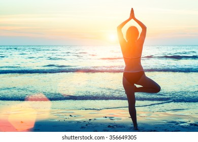 Yoga woman silhouette. Woman doing meditation near the ocean.