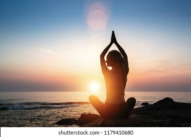Yoga woman silhouette meditation on the ocean during amazing sunset.