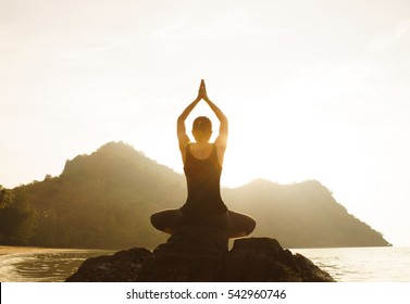Yoga woman sitting in lotus pose on the beach during sunset, Lens Flare