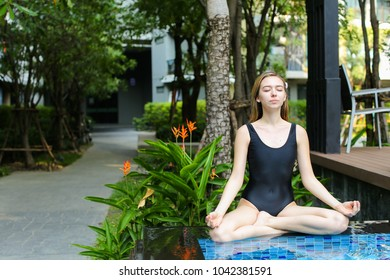 yoga woman sitting in lotus position by swimming pool on sunny day. concept of physical or mental action, supreme being or receive good karma