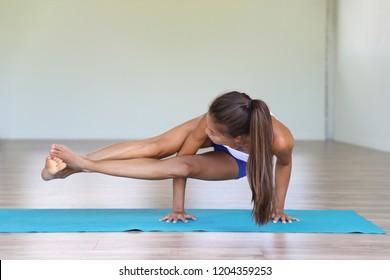Yoga woman strength training on exercise mat doing yoga poses exercises at gym. Difficult pose, astavakrasana, asymmetrical arm balance eight Angle Pose.