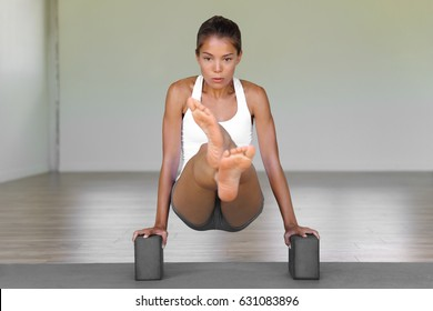 Yoga woman training core at fitness gym. Asian girl using yoga blocks for jump through movement floating legs using abs muscles. Fitness woman training core during yoga practice at gym studio.