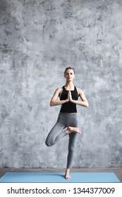 Yoga woman tree pose. Girl doing yoga exercises on a blue yoga mat full-length in the studio.