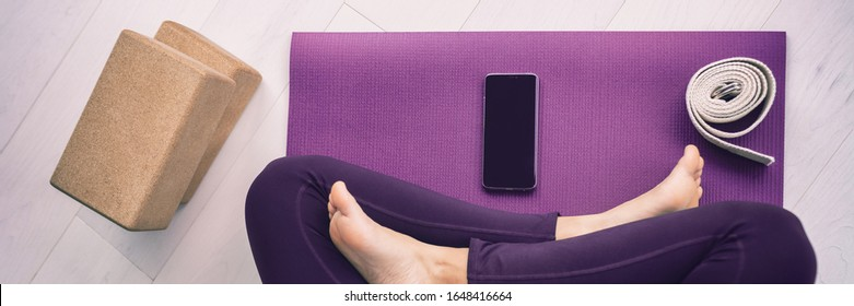 Yoga woman using mobile phone panoramic banner top view of cellphone on exercise mat and blocks, stretching strap.