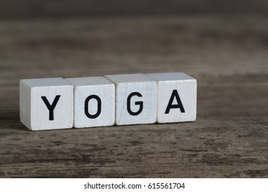 Yoga, written in cubes on a wooden background