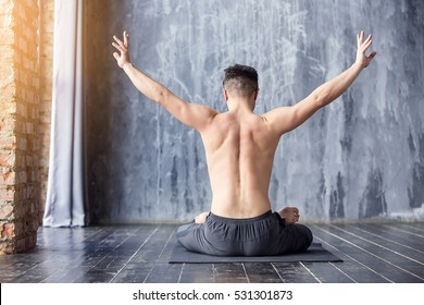 Yoga. Young caucasian yoga master practicing yoga near a window. Yogi men sitting in lotus pose and meditates on dark urban background indoors. Yoga men workout in studio on black mat, back view