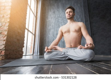Yoga. Young caucasian yoga master practicing yoga near a window. Yogi men sitting in lotus pose and meditates on dark urban background indoors. Yoga men workout in studio on black mat