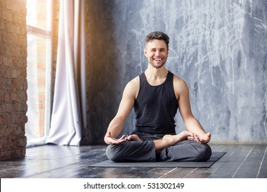 Yoga. Young caucasian yoga master smiling and looking at window. Yogi men sitting in lotus pose and meditates on dark urban background indoors. Yoga men workout in studio on black mat