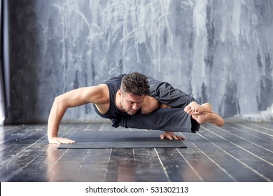 Yoga. Young man doing an asana ashtavakrasana. Hand standing pose. Yogi master workout on black mat on urban studio. Guy doing yoga indoors near a window, lifestyle healthy concept