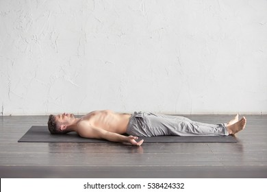 Yoga. Young men meditating on a wooden floor and lying in Shavasana pose. Yoga relax, meditating concept