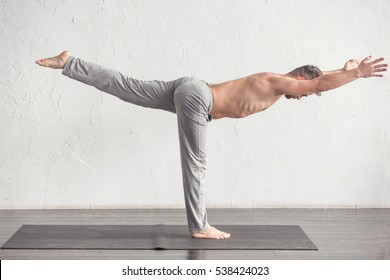 Yoga. A young strong man doing yoga exercises. Studio shot over white wall background and black floor.