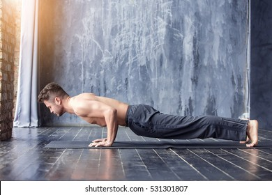 Yoga. Young yogi men practices yoga asana Chaturanga Dandasana - four-limbed staff pose in urban studio. Yoga men workout on black mat.