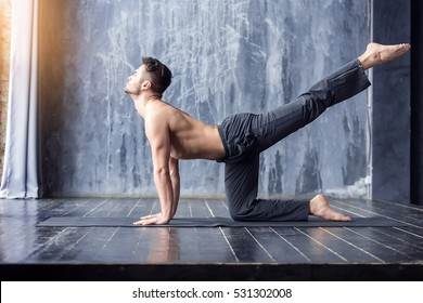 Yoga. Young yogi men practices yoga asana chakravakasana - dog pose in urban studio. Yoga men workout on black mat.