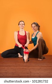 Yogasana instructor helps student stretch her leg