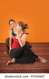 Yogasana trainer assisting student over orange background