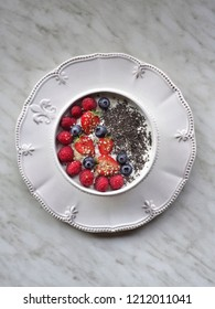 Yoghurt with berries (blueberries, strawberries and raspberries) and chia seeds in white bowl on white plate and white background. Overhead shot.