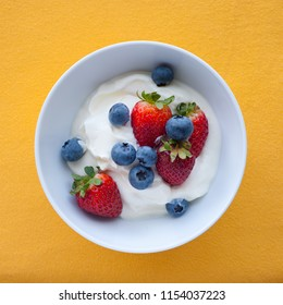 Yoghurt with strawberries and blueberries in bowl on yellow background, top view