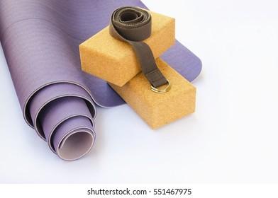 Yogi essentials. Lilac yoga mat, two cork blocks  and grey yoga strap on white background. Yoga practice concept.