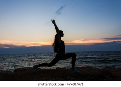 Yogi girl in a pose of a warrior on a cliff by the sea