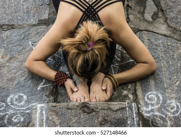 Yogi girl practicing paschimottanasana yoga pose, also known as forward bend pose from top, on stone floor in Mysore, India