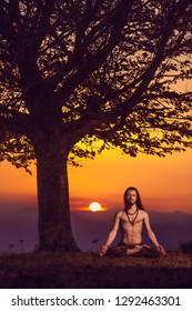 Yogi man meditating at sunset on the hills. Lifestyle emotional relaxation emotional concept spirituality harmony with nature