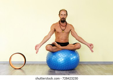 Yogi man practicing yoga with pilates ring on fitness ball in lotus pose