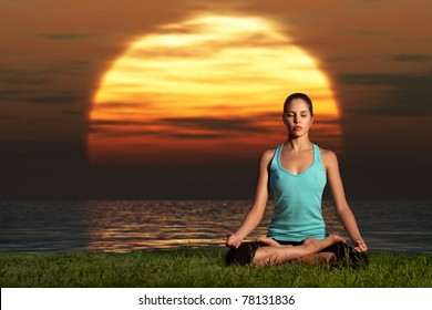Yogi sunrise. A sportive beautiful woman training yoga on the beach at dawn.
