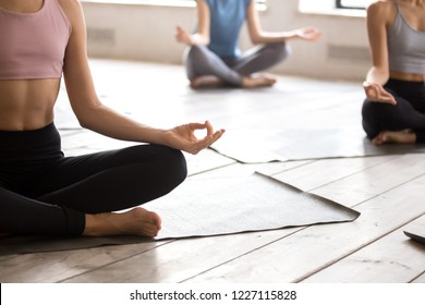 Yogi woman and group of young sporty people doing yoga Easy Seat exercise, Sukhasana pose, working out, indoor close up, female students training at club or studio. Well being, wellness concept