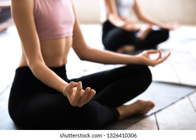 Yogi woman and a group of young sporty people practicing yoga lesson, doing Easy Seat exercise, Sukhasana pose with mudra, working out, indoor close up, students training at studio. Well-being concept