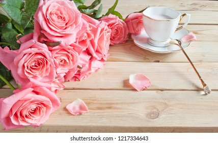 yogurt in beautiful cup and roses flowers bunch on wooden background