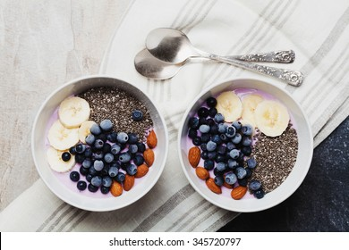 Yogurt with berries, banana, almonds and Chia seeds, bowl of healthy Breakfast every morning, vintage style, superfood and detox concept, top view