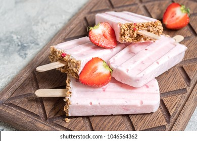 Yogurt, berry and granola breakfast popsicles on a tray