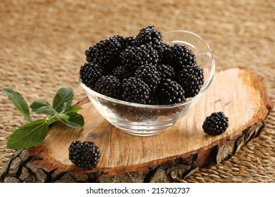 yogurt with blackberries in a glass jar and blackberries on a wicker mat background