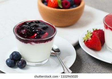 Yogurt with blueberries and blueberry flavoured preserve. Detail on one of several cups served on gray table