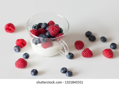 Yogurt with blueberries and raspberries in a glass Cup on a white background. Breakfast. Healthy diet