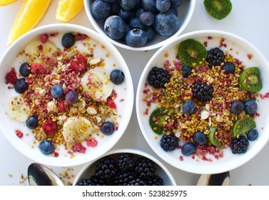 Yogurt breakfast bowls with granola, fruit, berries and superfoods