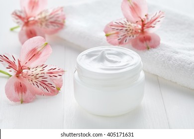 Yogurt cream natural organic beauty cosmetic product wellness and relaxation makeup mask in glass jar with pink flowers and towel on white background