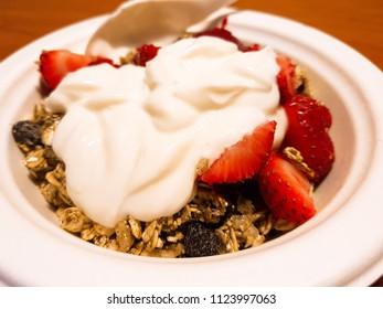 Yogurt dish with granola, and natural organic strawberries.