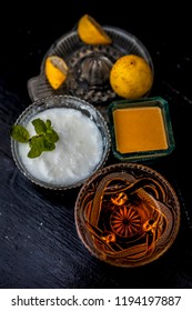 Yogurt face pack with raw lemon juice,honey and turmeric powder and yogurt or curd in a glass bowl on wooden surface,Close up view. For Acne prone skin.