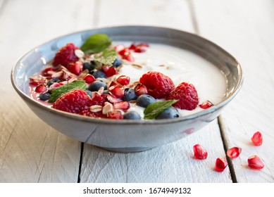Yogurt with fresh fruit and berries (raspberry, pomegranate, blueberry) and mint for healthy breakfast
