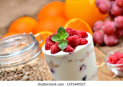 Yogurt, fresh raspberries in a glass and mint leaves, oranges, grapes and full glass of oatmeals in background - healthy breakfast concept